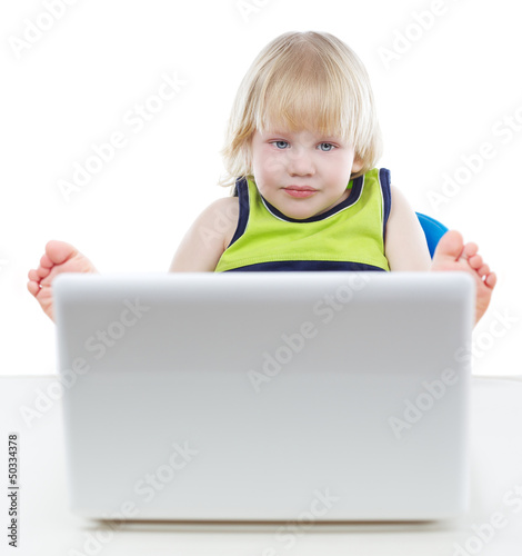 Young blonde boy looking at computer screen