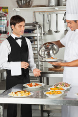 Chef Giving Customer's Food To Waiter