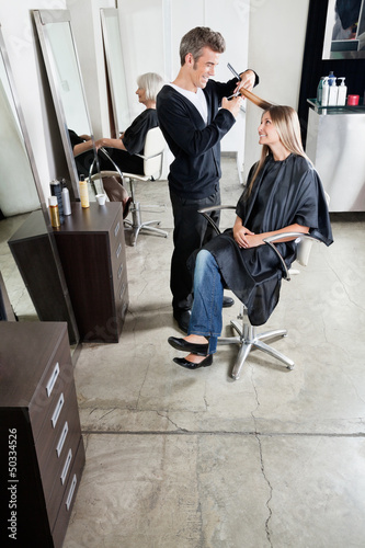 Hairstylist Cutting Customer's Hair In Salon