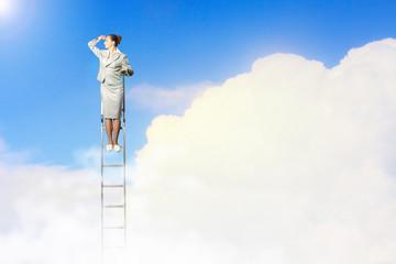 Businesswoman standing on ladder
