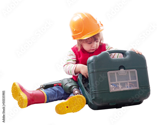 child in hardhat chooses tools in toolbox