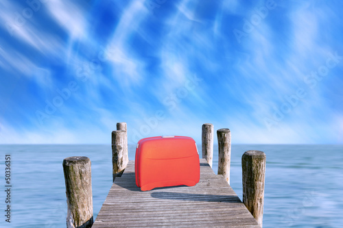 red suitcase parked on the pier