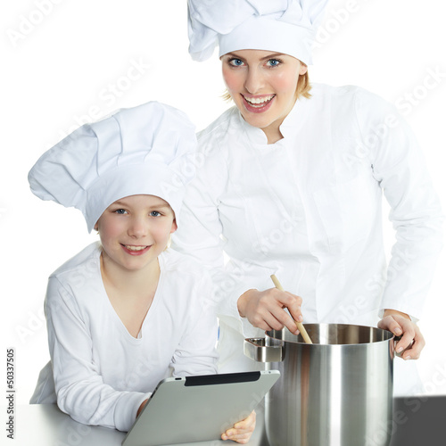 Mother and daughter using electronic tablet for cooking