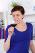 young woman enjoying a glass of red wine in her kitchen