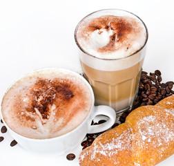 Kaffe, Latte Macchiato und Croissant vor weißem Hintergrund