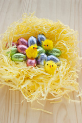Easter chocolate eggs nest with yellow chickens.