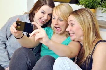 Freundinnen fotografieren sich mit Smartphone