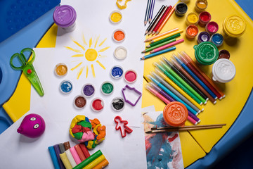 Table with color pencils, paints, playdough, felt pens and paper