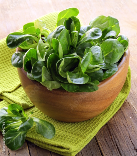 Fresh green salad valerian in a wooden bowl