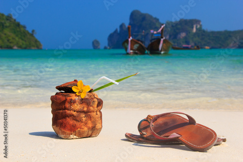 Coconut cocktail and sandals on the beach
