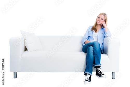blonde frau sitzt auf dem sofa