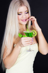 Sexy blonde girl with green cocktail