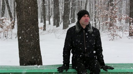 young man in a park in winter-sitting on a bench
