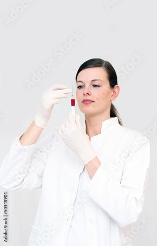 Ärztin untersucht Blutprobe in der Spritze