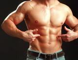 Muscular young man  showing abs.