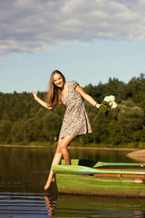 Young girl posing on boat with bouquet of flowers