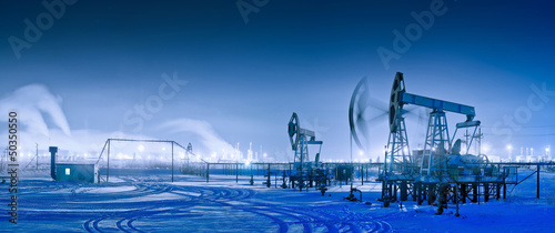 Leinwandbild Motiv Winter night panoramic oil pumpjack.