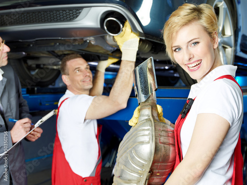 A team of car mechanics fixing the exhaust system of a car