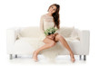 The beautiful woman. The woman in a white dress on a white sofa.
