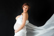 Redhead pregnant woman in white fabric