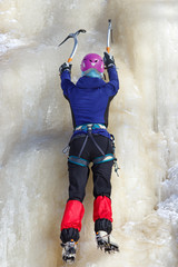 Female climber with ice tools on icy cliff