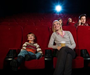Smiling mother and her son in cinema with other people behind th