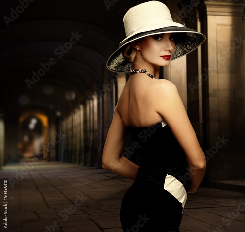 Woman in black dress and big white hat alone outdoors at night