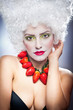 Woman with strawberry necklace, wig and professional makeup