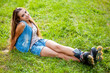 girl wearing roller skates sitting on grass