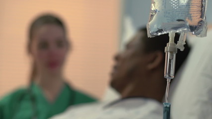 Close up of IV with nurse and patient in the background