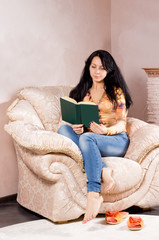 Woman curled up in an armchair reading
