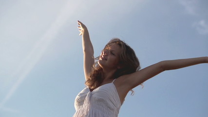 Happy beautiful woman stretching towards the sky, slow motion sh