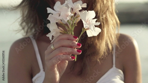 Young woman standing on seashore and smelling flower, slow motio