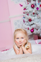The girl at the Christmas fir-tree with gifts