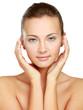 A beautiful young woman touching her face,