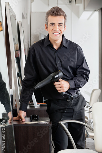 Happy Male Hairdresser With Hairdryer