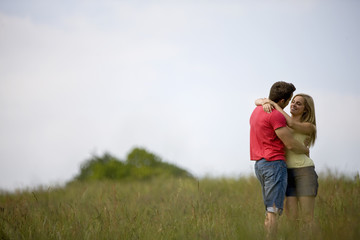 A young couple standing in a field embracing
