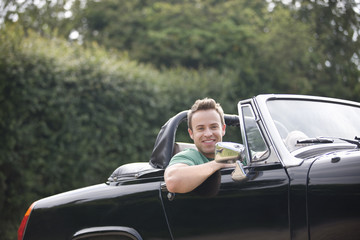 A young man sitting in a black sports car