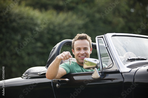 A young man sitting in a black sports car holding the keys