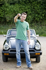 A young man holding the keys to his black sports car