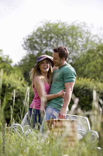 A young couple carrying a picnic basket in summertime