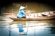Woman on wooden boat in river in Vietnam, Asia.