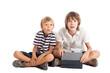 Постер, плакат: Два мальчика с планшетом сидят на полу удивленные лица