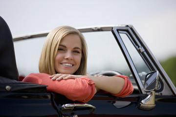 A young woman sitting in a black sports car