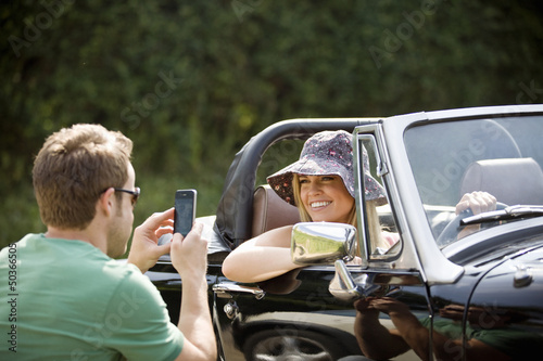 A young man photographing a young woman in a black sports car