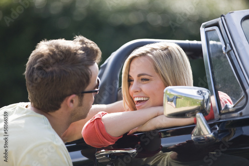 A young man speaking to a young woman in a black sports car