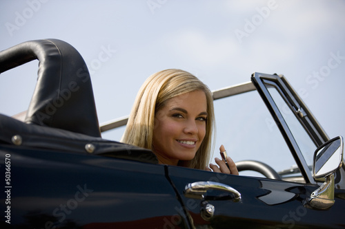 A young woman in a sports car holding a lipstick