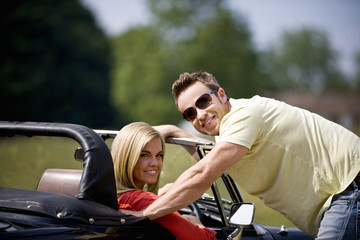 A young man standing next to a young woman in a black sports car