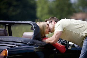 A young man kissing a young woman in a black sports car