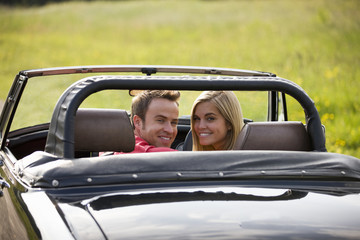 A young couple in a black sports car smiling